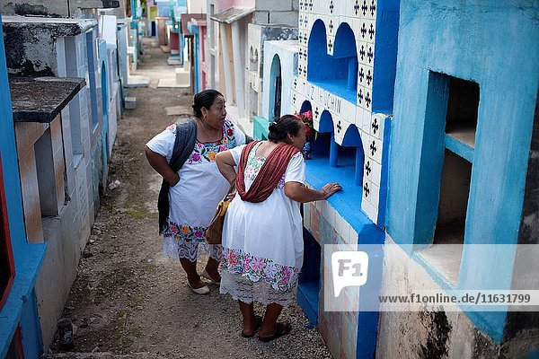 Mayan women visit the tomb of a deceased family member in the village of Pomuch  Hecelchakan  Campeche  Yucatán península  October 30  2016  as part of Day of the Dead celebrations in Mexico City  a Catholic celebration that honors the deceased. Pomuch is the only village in Mexico the neighboors clean the bones of their families.
