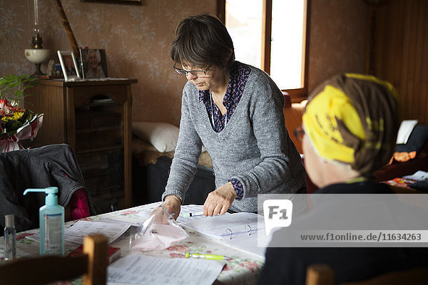 Reportage on a home health care service in Savoie  France. A nurse packs up the tubes for a blood test that she has just carried out on a patient with cancer.