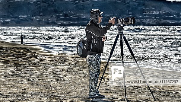 Photographer Aiming Camera with Telephoto Lens at Beach