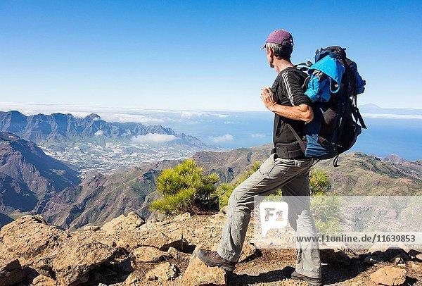 Mature male hiker on Alta Vista mountain on Gran Canaria with La Aldea de San Nicolas village in distance. Canary Islands. Spain.