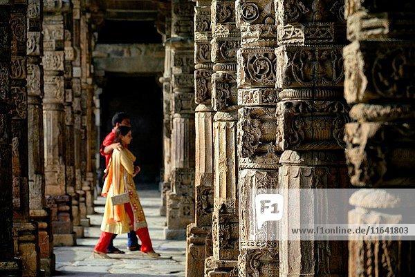 India  Delhi  Qutb Minar (Qutub  Qutab) listed as World Heritage by UNESCO  13th century minaret  72m high  14m diameter at the base  Indian couple walking beween columns