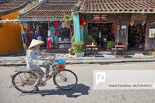 Woman rides bicycle in Hoi An Ancient Town. Quang Nam Province  Vietnam.