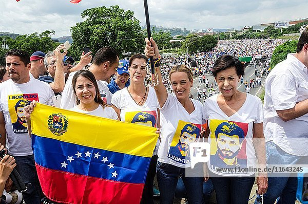 Lilian Tintori (2-R)  wife of prominent jailed opposition leader Leopoldo Lopez  Diana Lopez (1-L) sister and Antonieta Mendoza (1-R) mother of Leopoldo Lopez  holds a Venezuelan national flags as she marches against the government of President Nicolas Maduro in the streets of Caracas.