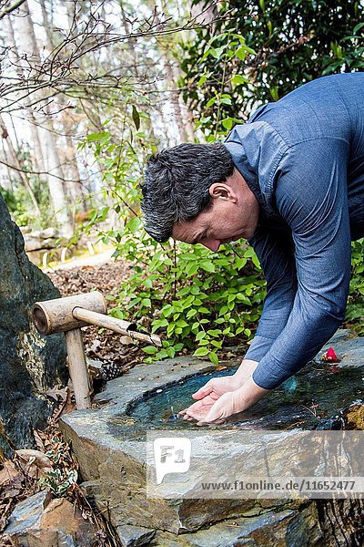 Caucasian handsome dark hair man putting his hands together to drink water out of a fountain in the wilderness.