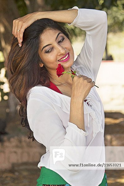 Smiling young woman holding at a rose.