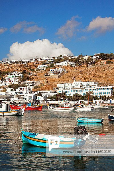 Colorful traditional fishing boats inside the harbor with the whitewashed traditional houses at the background  Mykonos  Cyclades Islands  Greek Islands  Greece  Europe.