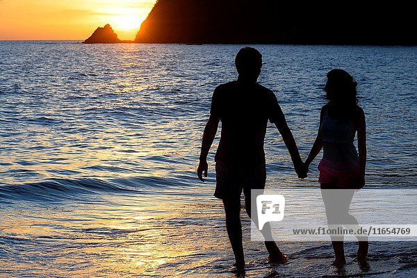 Couple lovers kissing at sunset in the beach. Kantiang Bay. Koh Lanta. Thailand. Asia. Kantiang Bay is most famous as the location of Pimalai  Koh Lantaâ.s first luxury hotel. There are now several other hotels  resorts and villas on Kantiang Bay which we recommend. Click on any link to view more photos  read guest reviews and book online. Kantiang Bay creates a perfect crescent shape to keep the Andaman Sea flat calm with crystal clear water. Looking up from the beach beyond the road  you will see the mountain range which provides breathtaking scenery around the bay. Even on a busy day you may find yourself sharing the beach with only a handful of people. Itâ.s a perfect choice for honeymooners and couples who want peace and quiet and get away from the masses. Ko Lanta is technically called Ko Lanta Yai  the largest of 52 islands in an archipelago protected by the Mu Ko Lanta Marine National Park. Almost all boats pull into Ban Sala Dan  a dusty two-street town at the northern tip of the island. Once the domain of backpackers and sea gypsies  Lanta hasn't just gentrified  it's morphed almost completely from a luscious southern Thai backwater into a midrange getaway for French  German and Swedish package tourists who come for her divine beaches (though the northern coast is alarmingly eroded) and nearby dive spots  Hin Daeng  Hin Muang and Ko Ha. Within eyeshot of Phi-Phi  Lanta remains far more calm and real  however  and effortlessly caters to all budget types. It's also relatively flat compared to the karst formations of its neighbours  and laced with good roads  so is easily explored by motorbike.