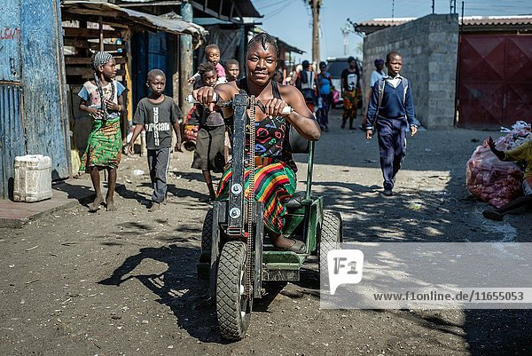 A girl rides a handbike at the local market accompanied by her friends from Home of Happiness for children with disabilities in Lusaka  Zambia.