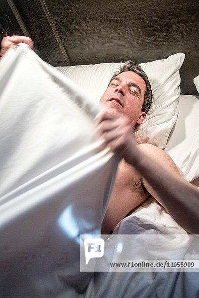 Caucasian male slepping  streching and waking up in bed.