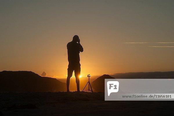 Man taking photos at golden hour in Galicia beach.
