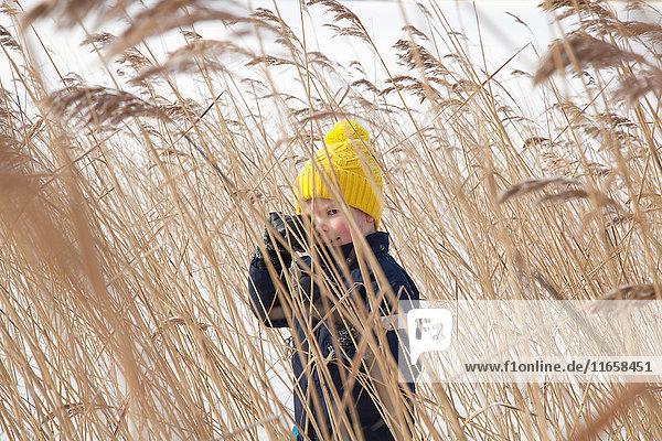 Junge steht im langen Gras  in schneebedeckter Landschaft