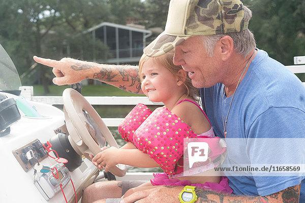 Tochter hilft Vater  Schnellboot zu steuern  Shalimar  Florida  USA