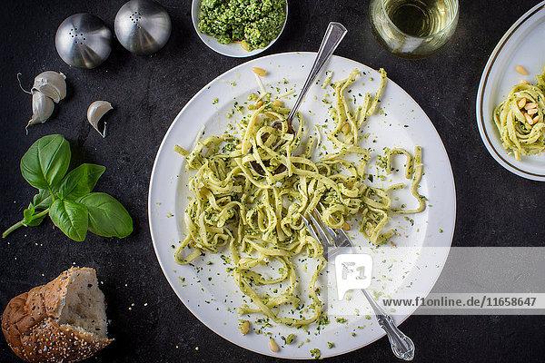 Ein verschlungener Teller Pesto-Nudeln mit Zutaten rund um den Teller und ein Glas Weißwein  Draufsicht