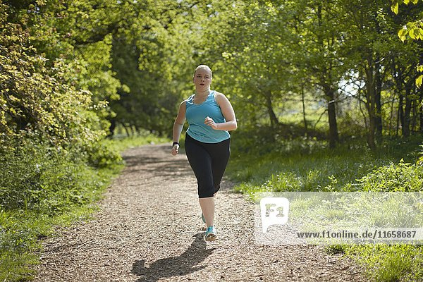 Young woman running on path.