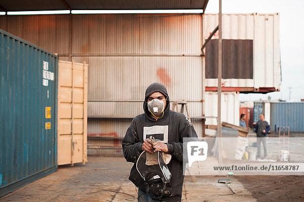Porträt eines Mannes auf einer Baustelle mit Schutzmaske