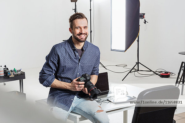 Portrait of male photographer sitting on desk in photography studio