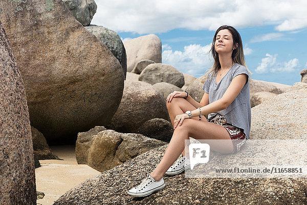 Teenagerin sitzt auf Felsen  Augen geschlossen  entspannt