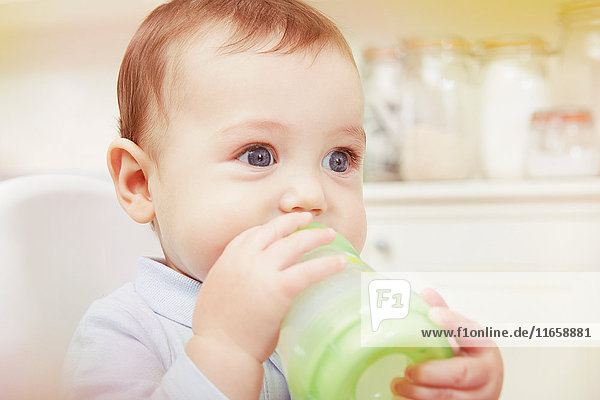 Blue eyed baby boy drinking from baby bottle