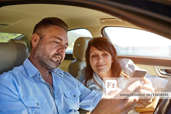 Couple in car  looking at smartphone