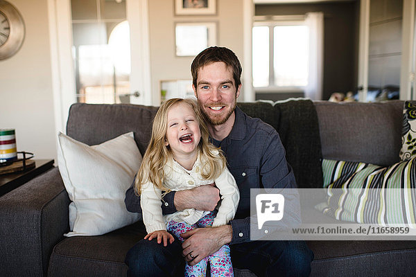 Portrait of man sitting on sofa with daughter on knee