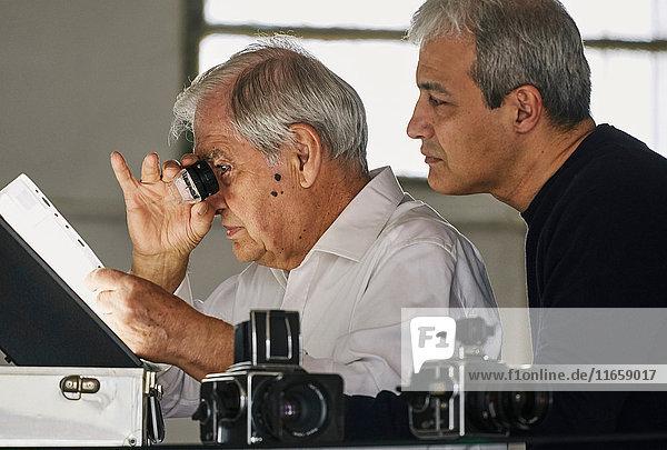 Vater und Sohn betrachten ein Blatt Filmdias