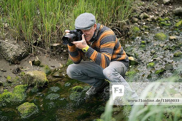 Mann kauert in flachem Fluss und fotografiert
