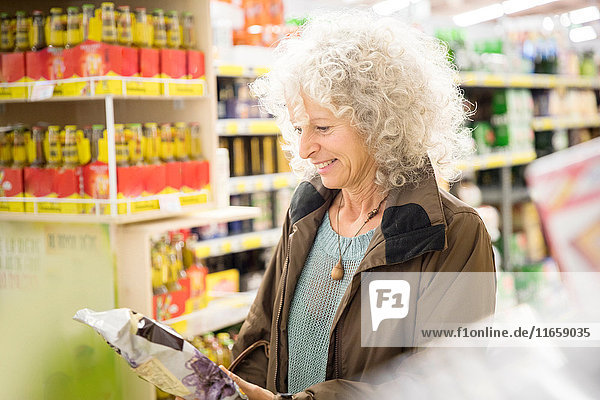 Mature woman in supermarket  reading back of packaging