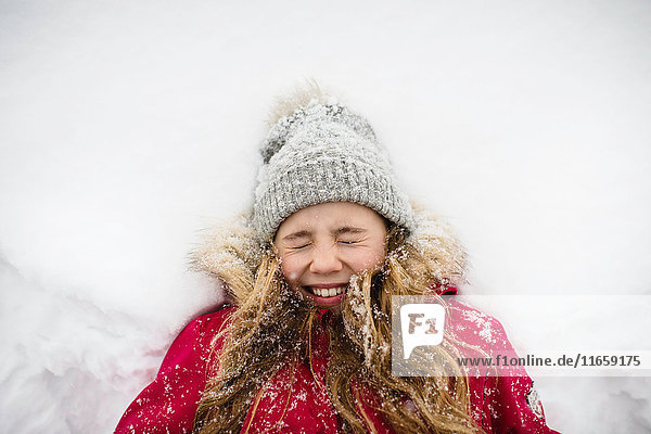 Girl lying on back in snow with eyes closed