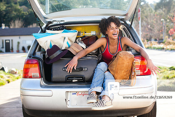 Woman sitting in car boot with luggage laughing