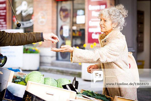 Reife Kundin kauft Gemüse auf dem lokalen französischen Markt