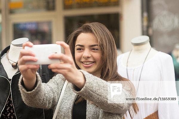 Junge Frau nimmt Smartphone-Selfie vor Marktstand-Puppen