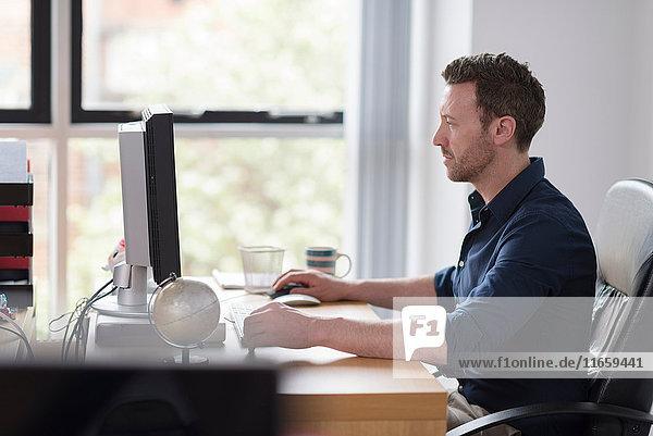 Am Computer arbeitender Mann am Büroschreibtisch