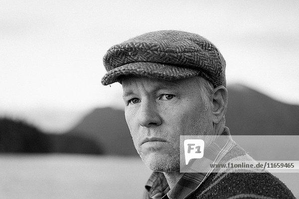 Porträt eines Mannes mit flacher Mütze beim Wegschauen