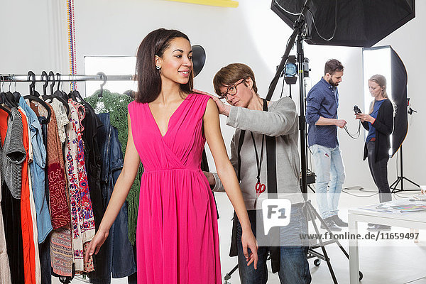 Stylist fastening fashion model's dress in photography studio