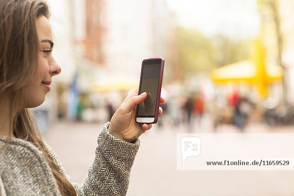 Junge Frau schaut auf Smartphone in der Fußgängerzone