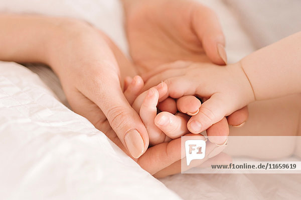 Mother holding baby's hands on bed