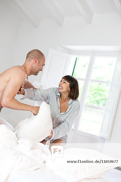 Ehepaar mit Kissenschlacht im Bett