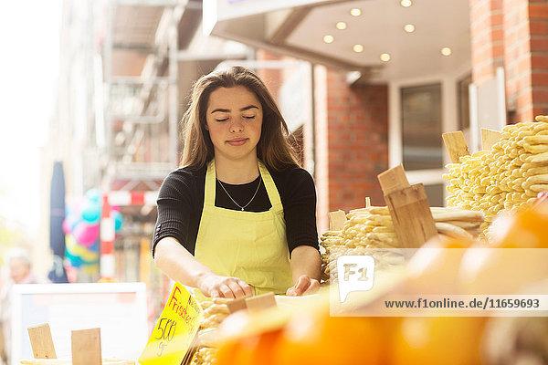 Junge weibliche Standhändlerin bereitet Brotstangenauslage vor