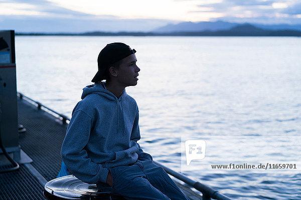 Teenager  der auf dem Dock sitzt und wegschaut  Pacific Rim National Park  Vancouver Island  Kanada