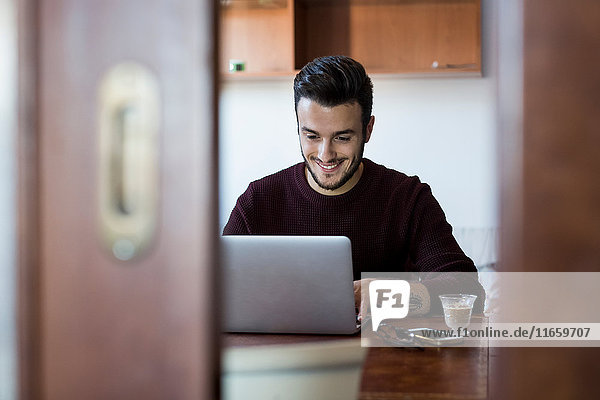 Young man sitting at table using laptop