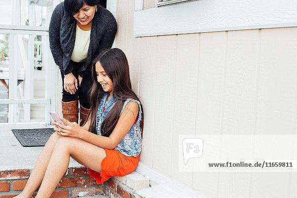 Mutter und Tochter auf der Veranda mit Blick auf Smartphone