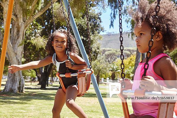 Zwei junge Schwestern spielen auf Parkschaukeln