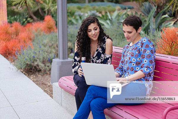 Zwei Frauen sitzen auf der Bank und schauen auf den Laptop