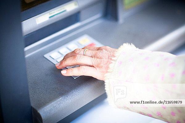 Hand der Frau beim Drücken der Tastatur am lokalen französischen Geldautomaten