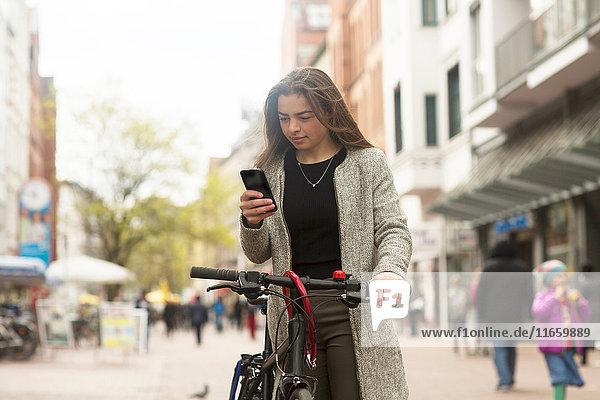 Junge Radfahrerin schaut auf Smartphone in Fußgängerzone