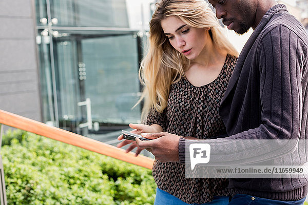 Young businessman and woman looking at smartphone in city