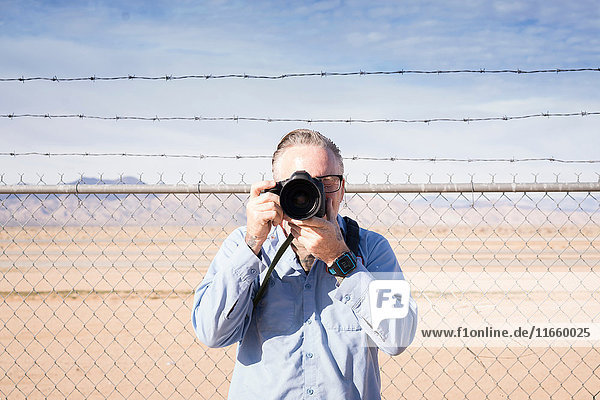 Photographer in front of barbed wire fence in desert taking photograph  California  USA