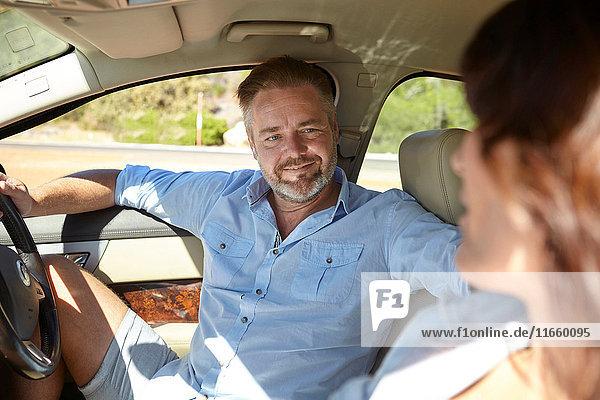 Ehepaar im Auto  Mann auf dem Fahrersitz  sitzend der Frau zugewandt