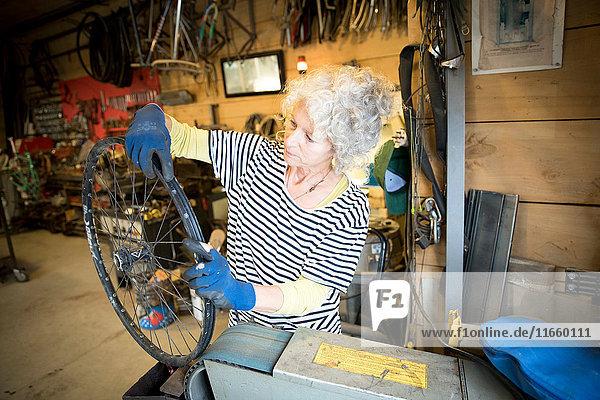 Frau  die in einer Fahrradwerkstatt arbeitet