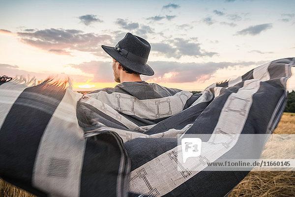 Mid adult man  standing in field  blanket around shoulders  rear view  Neulingen  Baden-Württemberg  Germany